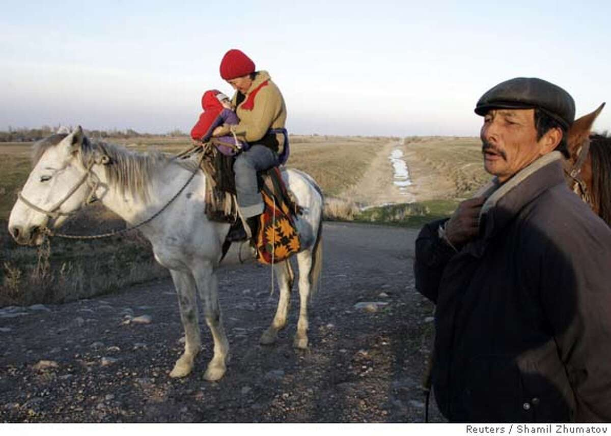 A Kazakh woman rides a horse with her child outside the village of Ashibulak, some 80 km (50 miles) east of Almaty, November 15, 2006. Many Kazakhs were upset by the British comedian Sacha Baron Cohen's film about the fictional TV journalist Borat, an anti-Semitic misogynist, who calls Kazakhstan his home. In an interview with Rolling Stone magazine released on Wednesday, Baron Cohen, 35, said he was surprised the film had caused such offence in Kazakhstan or that its humour had been so misinterpreted. Picture taken November 15. 2006. REUTERS/Shamil Zhumatov (KAZAKHSTAN) 0