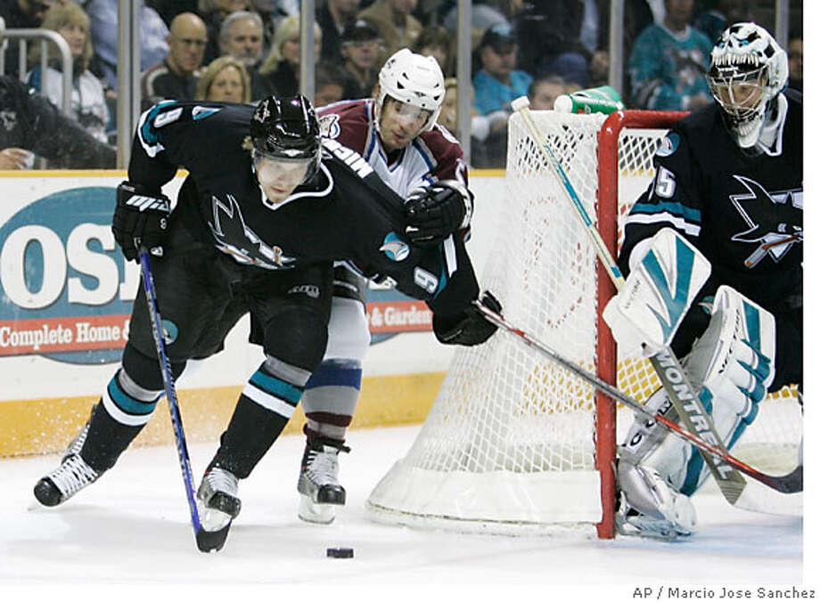 San Jose Sharks right wing Milan Michalek, left, of the Czech Republic, left, fights for the puck against Colorado Avalanche's Brett McLean, middle, as goalie Vesa Toskala, of Finland, looks on in the first period of an NHL hockey game in San Jose, Calif., Thursday, Dec. 7, 2006.(AP Photo/Marcio Jose Sanchez) Photo: MARCIO JOSE SANCHEZ