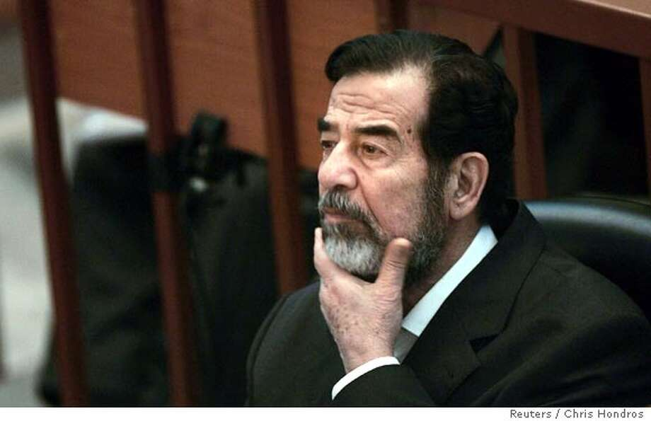 Saddam Hussein gestures in court during his trial in Baghdad December 7, 2006. Saddam appeared at his genocide trial on Wednesday, despite writing to the chief judge to say he would no longer attend court sessions in protest at being repeatedly silenced. Saddam and six others are on trial for the Anfal -- Spoils of War -- military campaign against ethnic Kurds in northern Iraq in the 1980s in which prosecutors say up to 180,000 people were killed in poison gas attacks and mass executions. REUTERS/Chris Hondros/Pool REUTERS (IRAQ)  Ran on: 12-08-2006  Saddam Hussein sat staring ahead, silent and impassive after the Anfal trial began. Photo: POOL