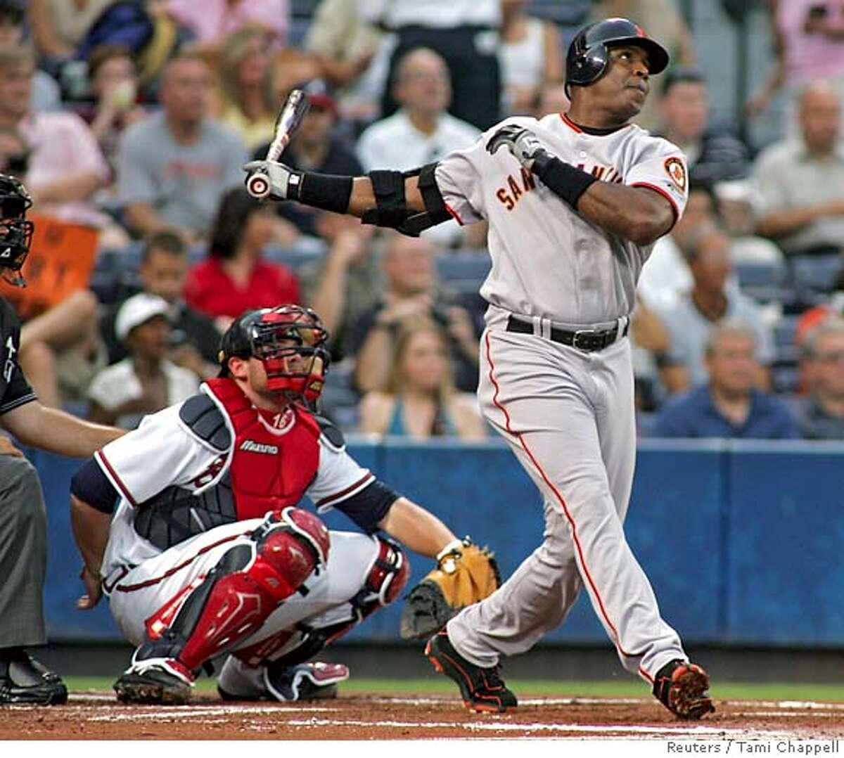 San Francisco Giants batter Barry Bonds watches his solo home run in the first inning with Atlanta Braves catcher Brian McCann (L) at their National League baseball game in Atlanta, Georgia, August 29, 2006. REUTERS/Tami Chappell (UNITED STATES)
