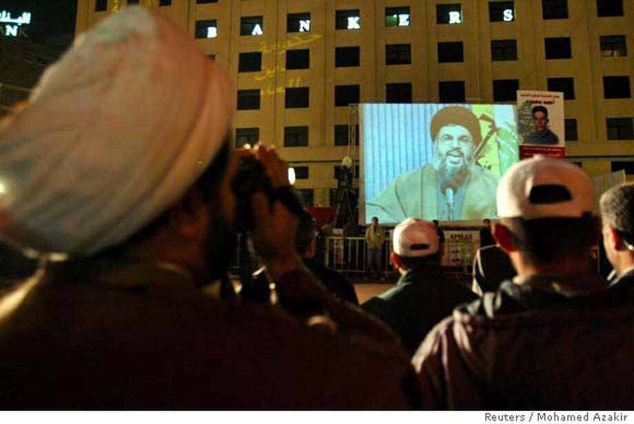 A Shi'ite sheikh (L) watches as Lebanese Hezbollah members stand guard during the seventh day of a rally held to demand the resignation of the U.S.-backed government as Hezbollah leader Sayyed Hassan Nasrallah speaks to demonstrators from a screen in central Beirut December 7, 2006. REUTERS/Mohamed Azakir (LEBANON)  Ran on: 12-08-2006  Hassan Nasrallah, the head of Hezbollah, rallies protesters in downtown Beirut to stand firm in their demand for the government of Lebanon to step down. Nasrallah's speech was broadcast on giant screens. Photo: MOHAMED AZAKIR