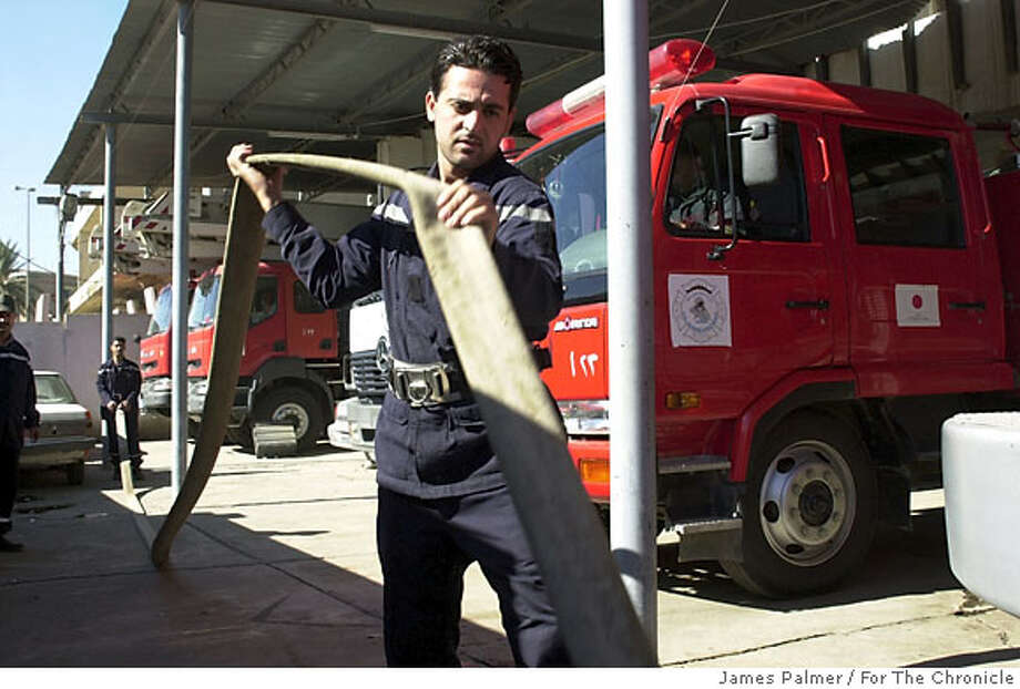 A firefighter unfurls a hose at the Karrada firehouse in the Al-Resafah District of Baghdad, Iraq, on Nov. 6, 2006. The soaring anarchy throughout Baghdad�s chaotic streets is increasingly thrusting the city�s 3,500 firefighters onto the frontlines of the war in Iraq and further complicating their already hazardous work. So far this year at least 30 Baghdad firemen have died in the line of duty and another 55 have been wounded, according to Iraq�s interior ministry, which oversees the country�s fire departments. PHOTO BY JAMES PALMER/FOR THE CHRONICLE Ran on: 12-08-2006  Baghdad's soaring turmoil is further complicating the already hazardous work of the city's 3,500 firefighters. Photo: JAMES PALMER/FOR THE CHRONICLE