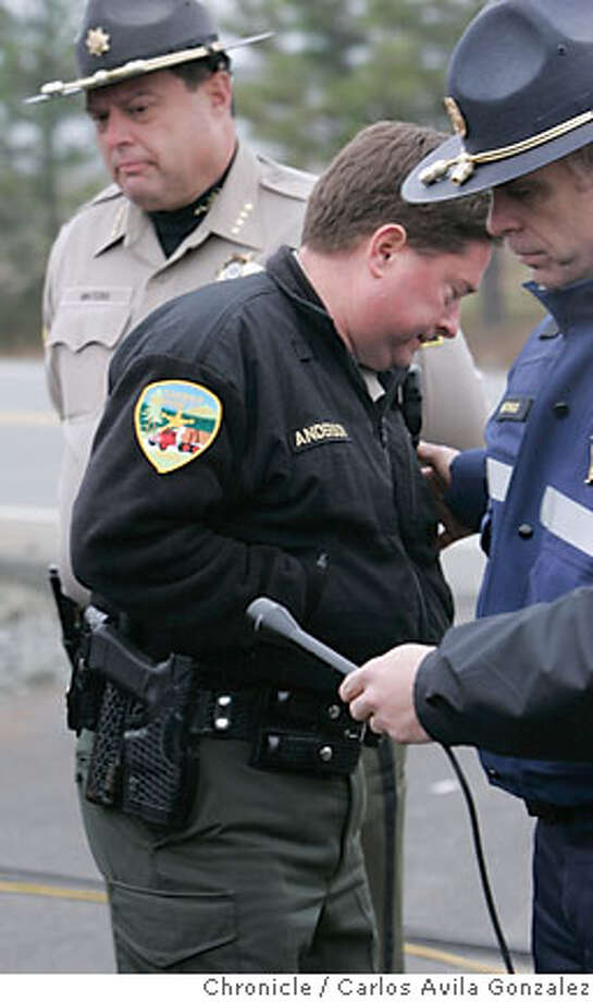 Josephine County Undersheriff Brian Anderson turns away from the news cameras as Oregon State Police Lt. Gregg Hastings consoles him after they announced that the body of James Kim had been located. Anderson was visibly upset by the news and could not finish his statement. Local and state authorities announced that their search for James Kim had concluded on Wednesday, December 6, 2006, after his body was discovered by search and rescue personnel. The San Francisco man whose family was rescued Monday after they were lost in the mountains outside of Merlin, Or., set out on foot to try to find help, but died as he attempted to bring assistance to his wife and two daughers.  Photo by Carlos Avila Gonzalez/The San Francisco Chronicle  Photo taken on 12/6/06, in Merlin, Or, USA.  **All names cq (source) Photo: Carlos Avila Gonzalez