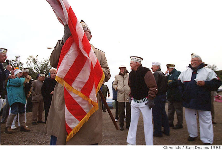PEARL 2/C/07DEC98/CZ/SD ---- Lloyd Prisk of Antioch rolls up Old Glory after a Pearl Harbor ceremony at Devils Elbow on Mount Diablo Monday where veterans gathered as the airplane beacon atop Mt Diablo was lit honoring Pearl Harbor survivors on Pearl Harbor Day. An icy road prohibited the vets from gathering on top the mountain at the beacon. (CHRONICLE PHOTO SAM DEANER) Photo: SAM DEANER