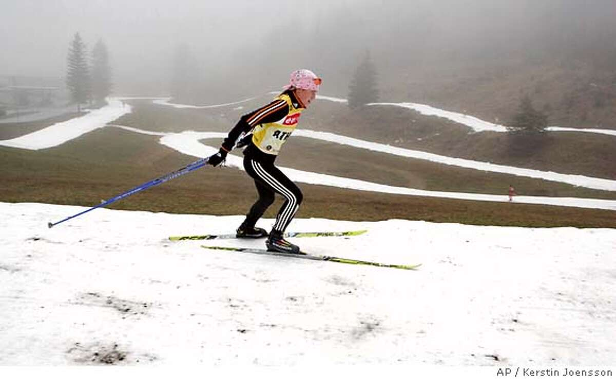 An unidentified athlete trains on a narrow snow track for the upcoming biathlon World Cup, on Tuesday, Dec 5, 2006, in Hochfilzen, Austria. Unusually warm temperatures and the lack of snow have caused problems for organizers of winter sports events. (AP Photo/Kerstin Joensson)