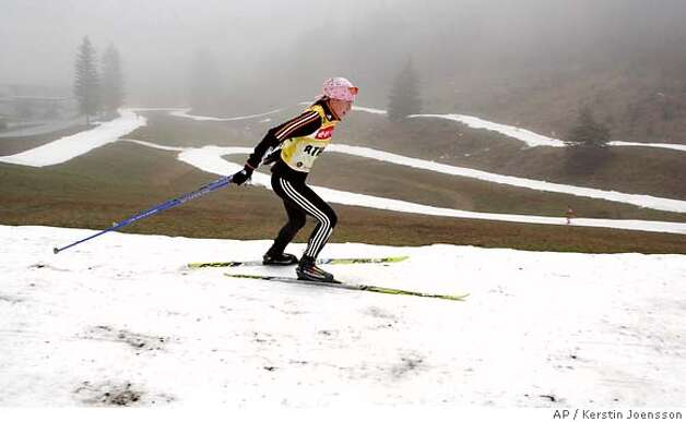 An unidentified athlete trains on a narrow snow track for the upcoming biathlon World Cup, on Tuesday, Dec 5, 2006, in Hochfilzen, Austria. Unusually warm temperatures and the lack of snow have caused problems for organizers of winter sports events. (AP Photo/Kerstin Joensson) Photo: KERSTIN JOENSSON