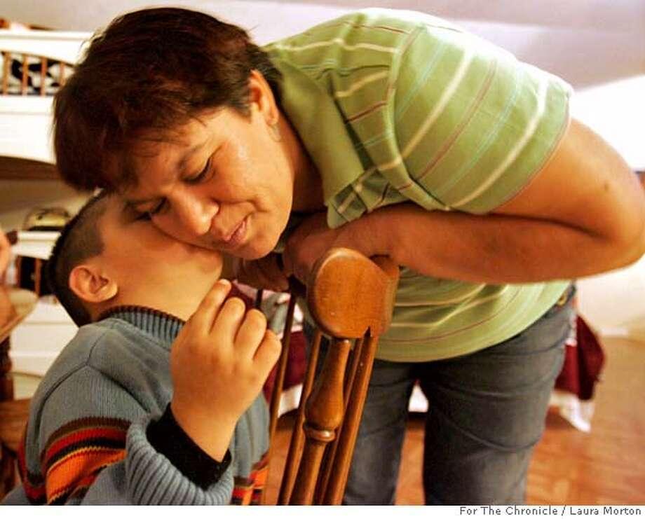 Three-year-old Brandon Nava gives his mom Silvia Nava a kiss after diner. Photo: Laura Morton