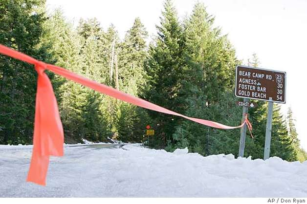 Red tape blocks the road to the Oregon coast along Bear Camp Road in the Siskyou National Forest near Galice, Ore., Tuesday, Dec. 5, 2006, near where the Kim family became stranded in snow. Kati Kim and her two children were found in good health Monday by a helicopter, but James Kim, who tried to hike out, is still missing as of Tuesday morning. (AP Photo/Don Ryan) Photo: Don Ryan