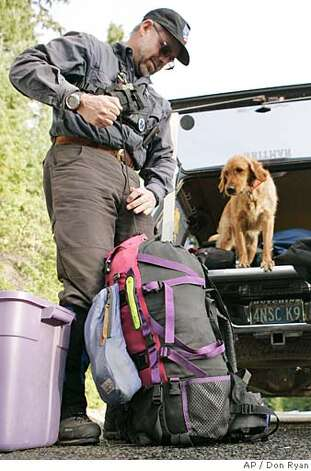 Searcher Scott Robbins, from Bend, Ore., prepares to take his scent-sniffing dog, Cali, in search of James Kim on Bear Camp Road in the Siskyou National Forest near Galice, Ore., Tuesday, Dec. 5, 2006, near where the Kim family became stranded in snow. Kati Kim and her two children were found in good health Monday by a helicopter, but James Kim, who tried to hike out, was still missing as of Tuesday morning. (AP Photo/Don Ryan) Photo: Don Ryan