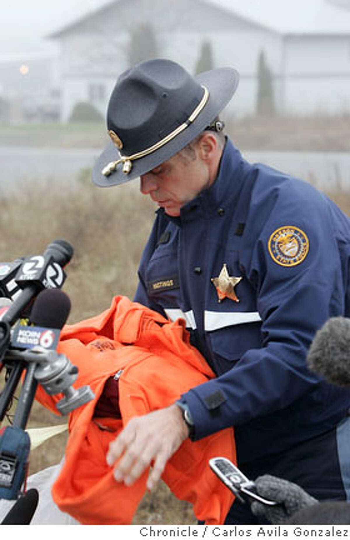 Oregon State Police Lt. Gregg Hastings shows some of the items that will be dropped as care packages for James Kim as part of the search and rescue as the hunt for James Kim continues on Wednesday, December 6, 2006. The package includes bright orange sweatshirt and pants, flares, MRE (meal-ready-to-eat), blanket, water-proof bib overalls, and personal letters from his family. Local and state authorities and search and rescue personnel continued their search for James Kim on Wednesday, December 6, 2006. The San Francisco man whose family was rescued Monday after they were lost in the mountains outside of Merlin, Or., set out on foot to try to find help, but has not been located. Photo by Carlos Avila Gonzalez/The San Francisco Chronicle Photo taken on 12/6/06, in Merlin, Or, USA. **All names cq (source)