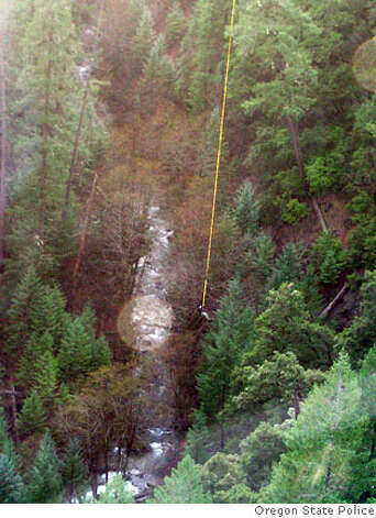A searcher is lowered on a line via helicopter into the Big Windy Creek area of Siskiyou National Forest near Galice, Ore., Tuesday, Dec. 5, 2006, to assist with the search for James Kim. Kim, who became stranded in the southern Oregon mountains with his wife and two daughters, tried to walk out Dec. 2, 2006 and has been missing since. Kim's wife, Kati, and their two daughters, Penelope and Sabine, were rescued Monday.(AP Photo/Oregon State Police/HO)