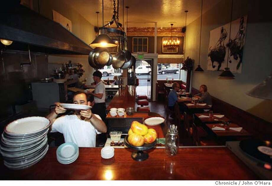 Blue Plate's narrow front room has a long bar facing an open kitchen. Chronicle photo by John O'Hara