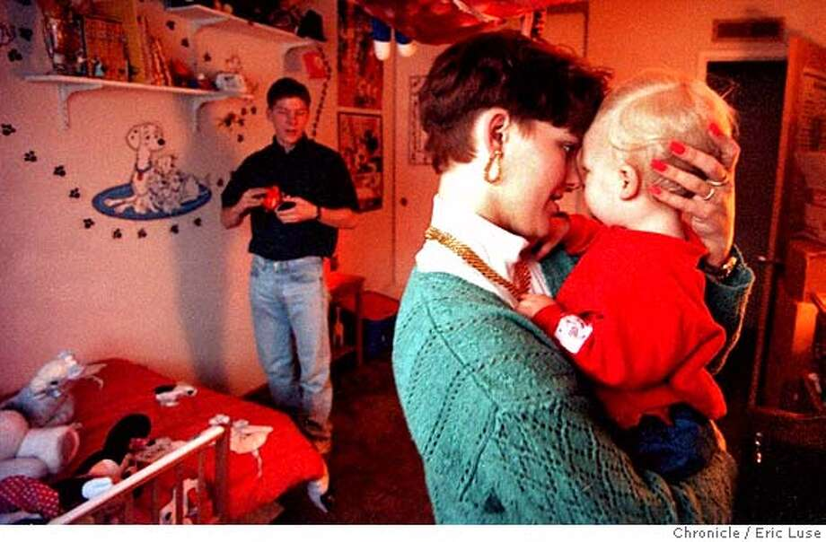 CHRONICLE 01/08/94 // JENNIFER STOLPA HOLDS BABY CLAYTON WITH HUSBAND JIM STOLPA IN THE BACKGROUND CAT Photo: ERIC LUSE