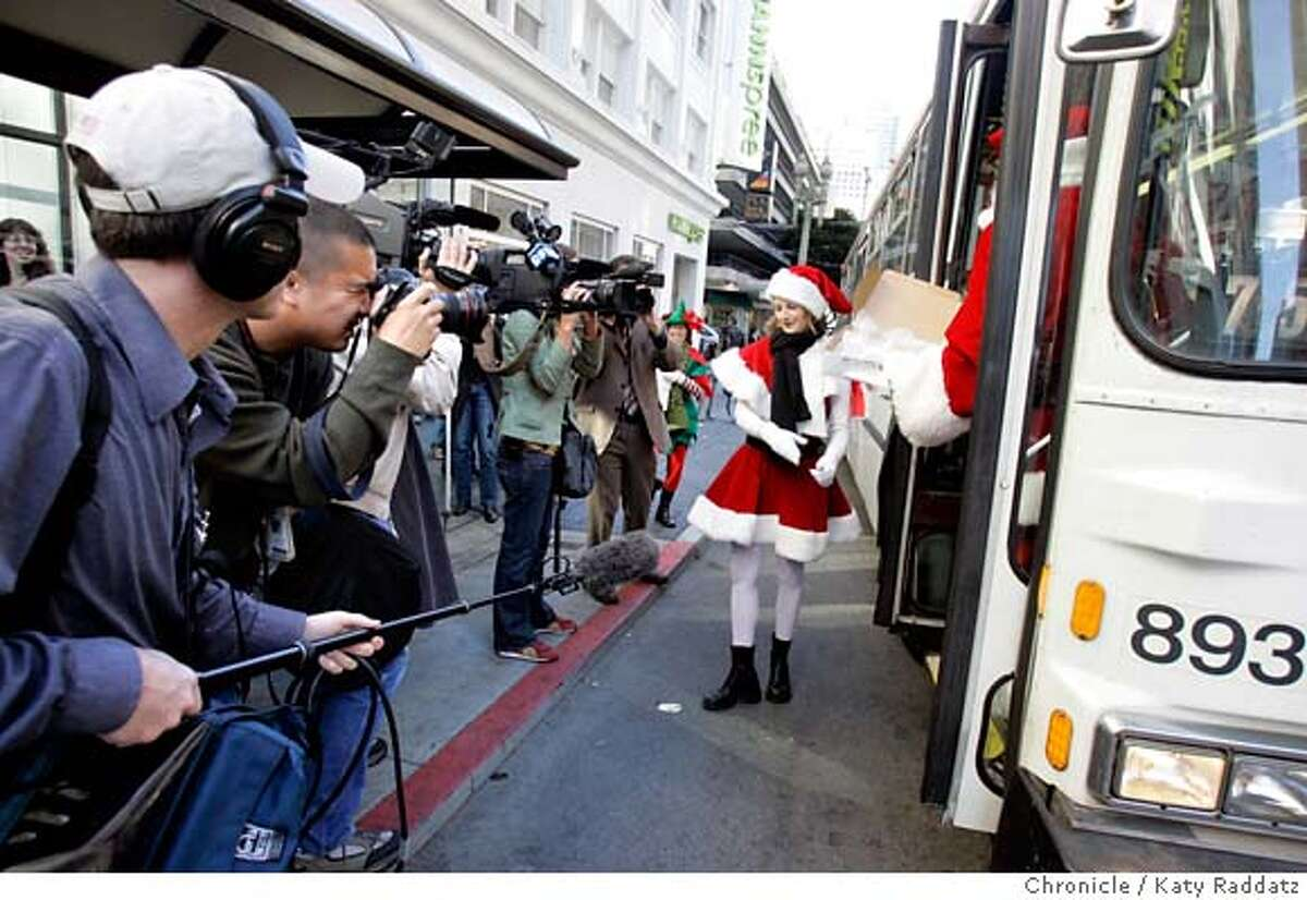 """COOKIES05_029_RAD.jpg SHOWN: It's a media event: Santa and his Helpers have handed out cookies to waiting Muni passengers, and now bid goodbye to them as the bus pulls away--Santa, played by Charles Jennings just has time to disembark, and his helper, played by Molly Richardson, smiles for the assembled press. Story is about the reaction to the chocolate smell wafting from Muni bus shelters with the """"Got Milk?"""" ads. We go to the bus shelter on the NW corner of Sutter and Stockton Sts. Rachel Gordon is the writer for Metro. These photos were made on Monday, Dec. 4, 2006, in San Francisco, CA. (Katy Raddatz/SF Chronicle) * Mandatory credit for the photographer and the San Francisco Chronicle. ; mags out."""