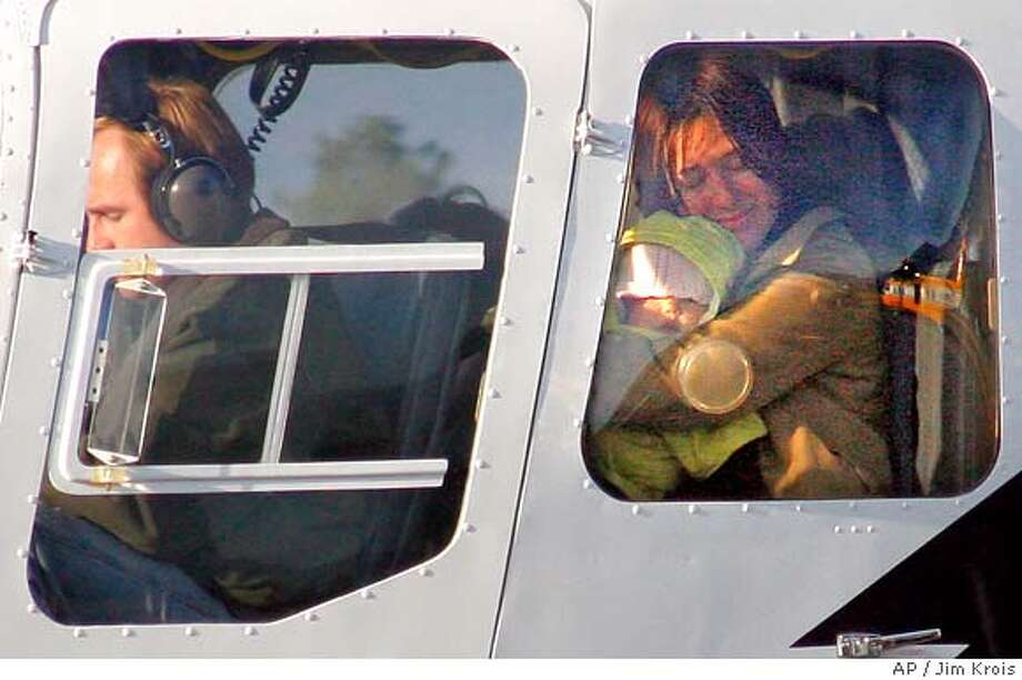 Kati Kim holds her daughter, seven-month old, Sabine Kim, in the back of a helicopter after they and her other daughter, Penelope, 4, were rescued from a remote area of southern Oregon, Monday, Dec. 4, 2006. They were airlifted to Three Rivers Community Hospital in Grants Pass. James Kim, 35, Kati's husband is still missing. (AP Photo/Grants Pass Daily Courier, Jim Krois) Photo: JIM KROIS