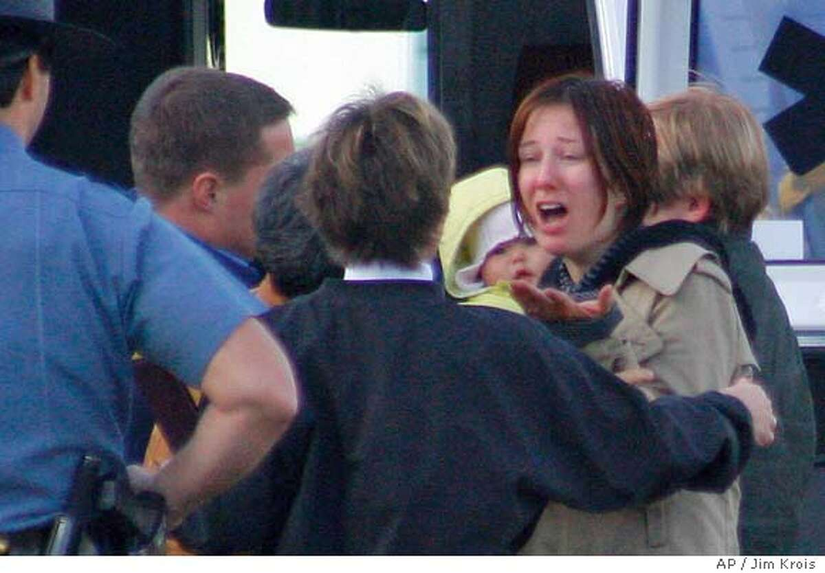 Kati Kim, right, talks to rescue personnel Monday, Dec. 4, 2006, after she and her two daughters, Sabine, 7 months, in yellow, and Penelope, 4, were rescued in the mountains of southwest Oregon about 35 miles west of Grants Pass, Ore. Her husband, James Kim, is still missing. (AP Photo/Grants Pass Daily Courier, Jim Krois)