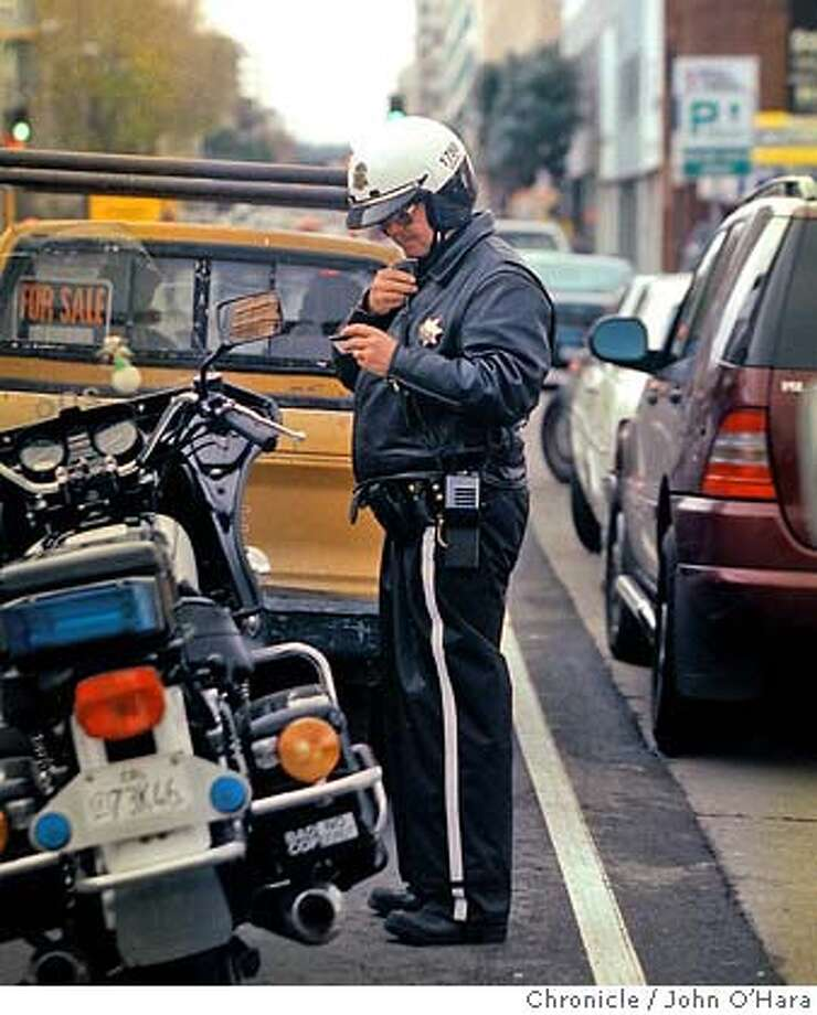 "STOPSQUAD-C-25JAN00-MN-JO  San Francisco, CA. Folsom btwn 5th and 4th sts.  Officer Les Adams, a member of the ""Stop Squad"" a 4-KING unit. Eight Officers hunt out expired license plate tags. An expired tag, can mean that the vechile owner has a suspended Drivers License, If that is the case, the vehicle is immediatley siezed. This truck, with expired tags, also had a broken front window, and the occupants were not wearing seat belts. And the ticket was issued.  Photo by............John O'Hara Photo: JOHN O'HARA"