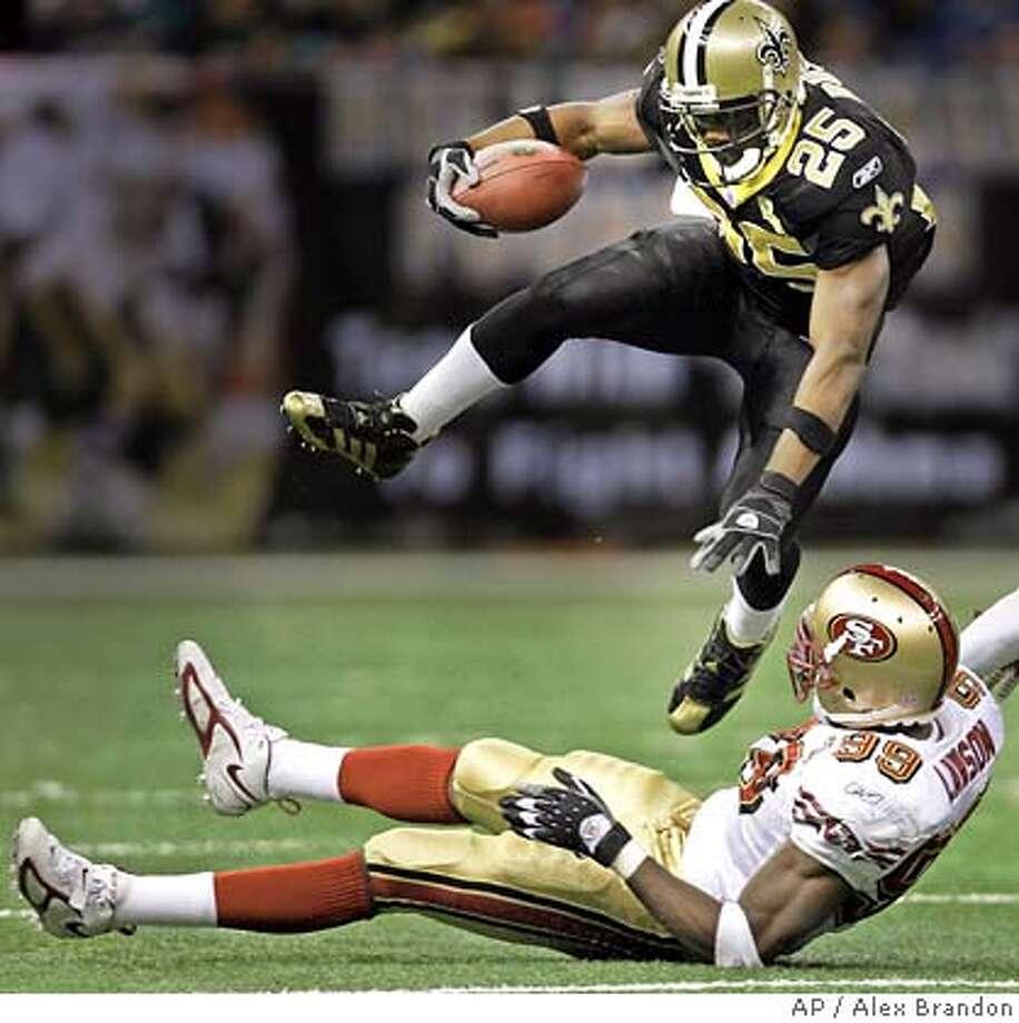 New Orleans Saints running back Reggie Bush jumps over San Francisco defender Manny Lawson (99) in the first half of their NFL football game in New Orleans, Sunday, Dec. 3, 2006. (AP Photo/Alex Brandon) Photo: ALEX BRANDON