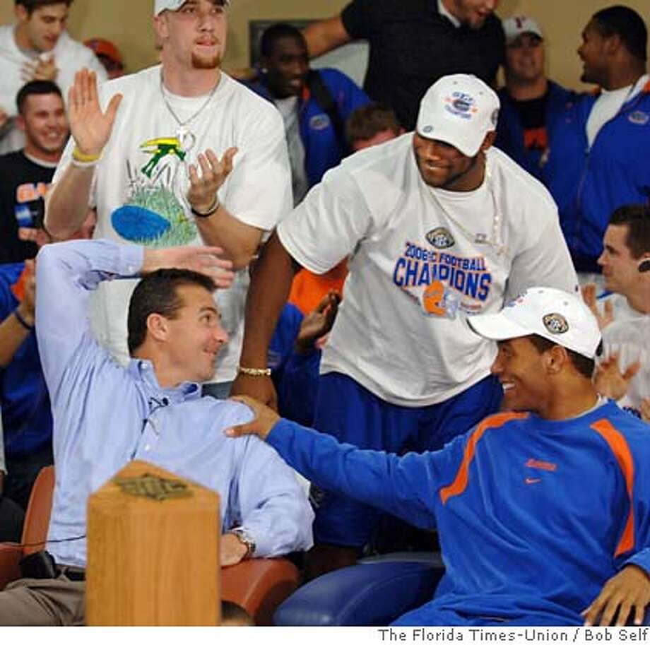 Florida football coach Urban Meyer, left, is congratulated by players, Chris Leak, foreground right, Tate Casey, background left, and Brandon Siler, standing at right, after the announcement that they will be playing Ohio State for the college football national championship, Sunday night, Dec. 3, 2006, at Ben Hill Griffin Stadium in Gainesville, Fla. (AP Photo/The Florida Times-Union, Bob Self) ** MAGS OUT, TV OUT ** MAGS OUT, TV OUT EFE OUT Photo: BOB SELF