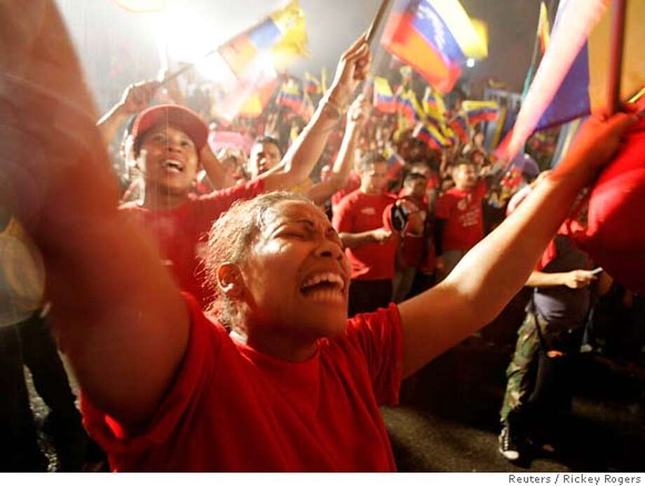 "Supporters of Venezuelan President Hugo Chavez celebrate in the rain in front of the Miraflores Palace as Chavez gives a speech from the balcony after official election results gave him a victory by a wide margin in Caracas December 3, 2006. The anti-U.S. Venezuelan president claimed victory with a cry of ""long live the revolution"" as official results showed him heading for a landslide re-election win on Sunday. REUTERS/Rickey Rogers (VENEZUELA) 0 Photo: RICKEY ROGERS"