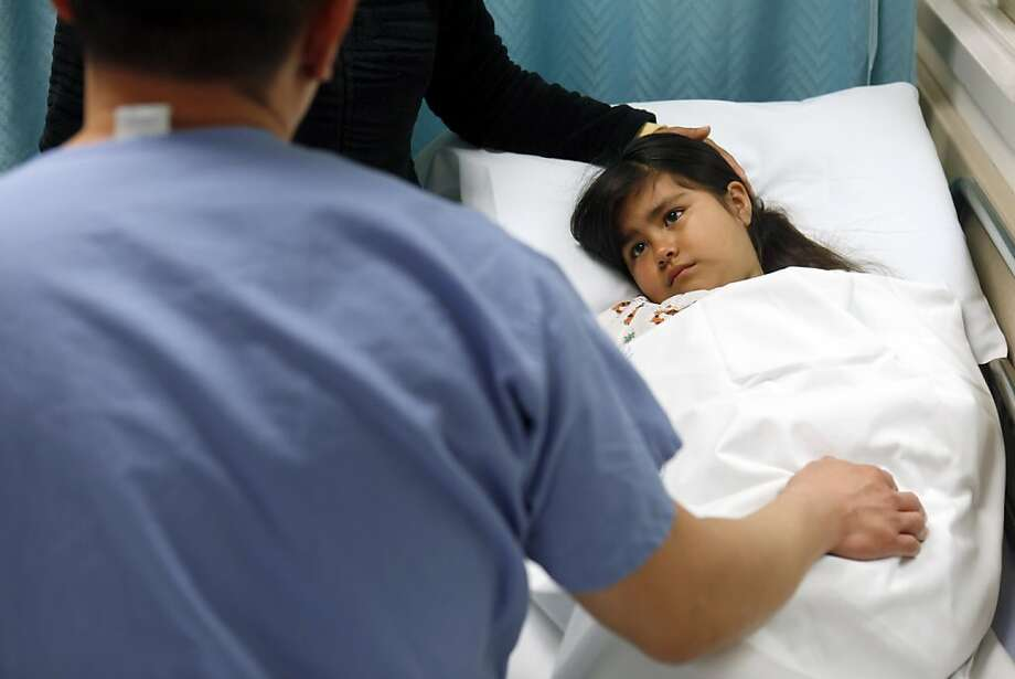 Dr. Tony Yuan checks Atzhiry Perez, 7, at the St. Rose Hospital emergency room on Thursday, March 15, 2012. St Rose Hospital in Hayward, Calif., is in dire financial straits, the charity hospital treats anyone who walks in the door, regardless of whether they have insurance. Alameda County, Kaiser, Washington Hospital in Fremont and others are now cobbling together emergency funding to keep the place open. Photo: Carlos Avila Gonzalez, The Chronicle