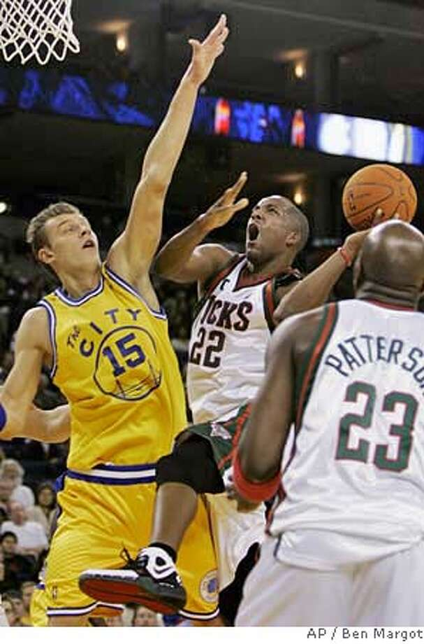 Golden State Warriors' Andris Biedrins (15), of Latvia, tries to block the shot of Milwaukee Bucks' Michael Redd during the first quarter of an NBA basketball game Saturday, Dec. 2, 2006, in Oakland, Calif. Watching the play at right is Bucks' Ruben Patterson. (AP Photo/Ben Margot) Photo: BEN MARGOT