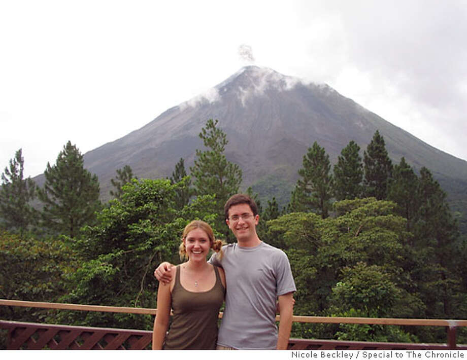 Dec. 3  TRAVEL JUSTBACK -- Nicole Beckley and Alex Marshall in front of the Arenal Volcano in Costa Rica. 7/8/06 in , . / Special to The Chronicle Photo: Nicole Beckley