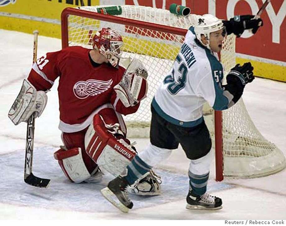 San Jose Sharks center Joe Pavelski (R) celebrates his game winning goal against Detroit Red Wings goalie Joey MacDonald during the third period of their NHL game in Detroit, Michigan December 2, 2006. REUTERS/Rebecca Cook (UNITED STATES) Photo: REBECCA COOK
