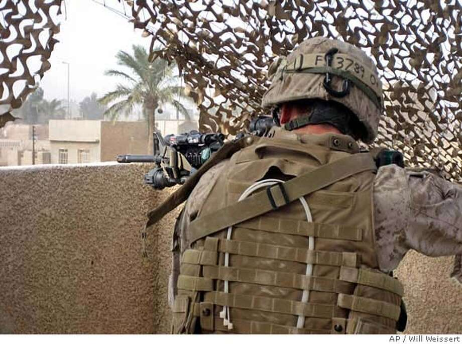 Lt. Richard Jahelka, of the 2nd Battalion, 4th Marines, aims at possible insurgents from the roof of a U.S. outpost in central Ramadi, a dangerous city choked with insurgents and the capital of the volatile province of al-Anbar, west of Baghdad, Saturday, Dec. 2, 2006. Jahelka is part of the 15th Marine Expeditionary Unit, temporarily deployed from its ships in the Persian Gulf to provide reinforcements in Anbar. (AP Photo/Will Weissert) Photo: WILL WEISSERT