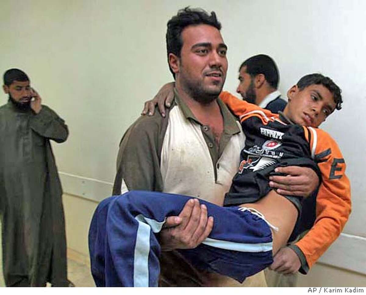 An Iraqi youth injured in an explosion is carried at a hospital in Baghdad, Iraq, Saturday, Dec. 2, 2006. A triple car bombing struck a food market in a predominantly Shiite area in central Baghdad on Saturday, killing at least 51 people a day after a U.S.-Iraqi raid against Sunni insurgents in a nearby neighborhood. (AP Photo/Karim Kadim)