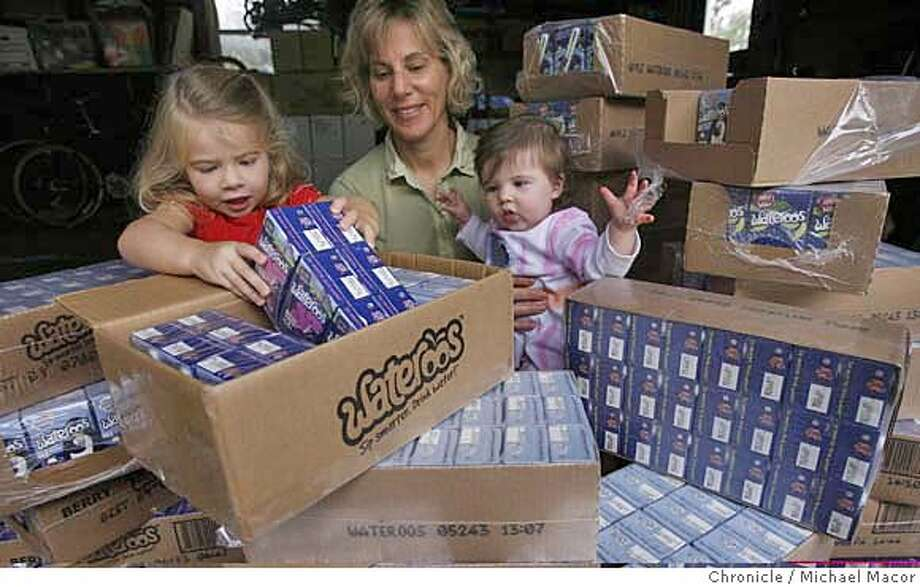 Roberta Greenspan with daughters, Megan, 4 and Paige, 5 months. Boxes of their product stored in the family garage. Parent entrepreneurs, people who start businesses based on needs they discover while raising their own kids. This photo is of Roberta Greenspan, a former software executive who has started a business producing Wateroos, beverage boxes like juice boxes only filled with water. Greenspan got the idea for the business because she didn't want to give her daughter sweetened juices, but plastic sippy cups kept leaking in her purse. Event in, Hayward, Ca, on 11/17/06. Photo by: Michael Macor/ San Francisco Chronicle Photo: Michael Macor
