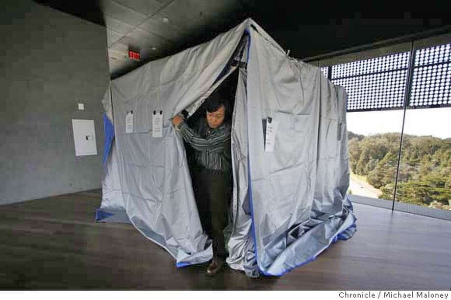 Photographer Shi Guorui exits the tent where he will stay inside during exposures up to 90 minutes.  Noted chinese photographer Shi Guorui is making a series of panoramic images of SF using a camera obscura. On this day, he has set up the tent like camera in the tower of the de Young Museum in GG Park. Photo by Michael Maloney / San Francisco Chronicle on 10/25/06 in San Francisco,CA MANDATORY CREDIT FOR PHOTOG AND SF CHRONICLE/ -MAGS OUT Photo: Michael Maloney