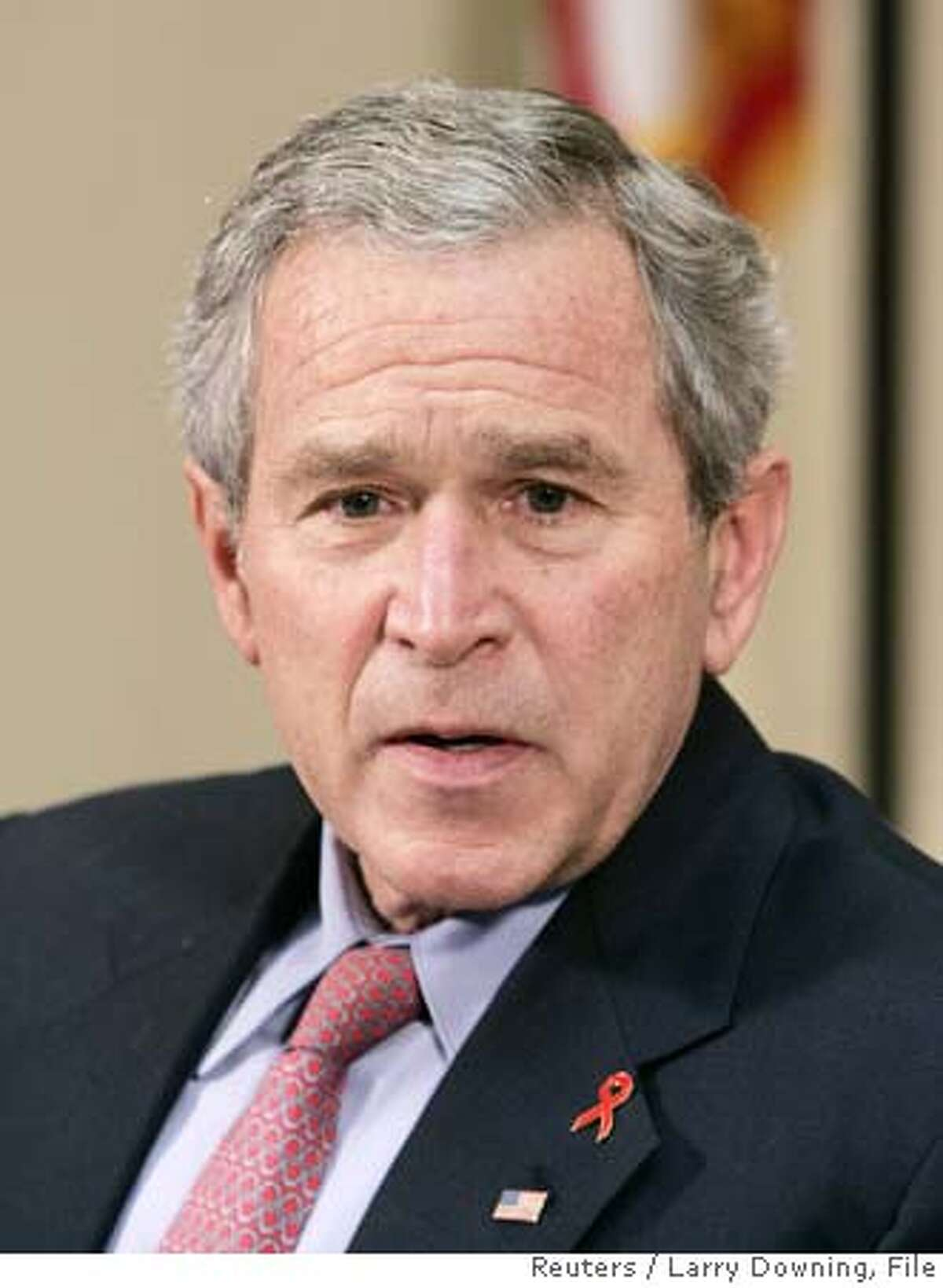 U.S. President George W. Bush, wears an AIDS Awareness lapel pin while hosting a meeting on World AIDS Day in the Roosevelt Room at the White House in Washington December 1, 2006. REUTERS/Larry Downing (UNITED STATES) 0