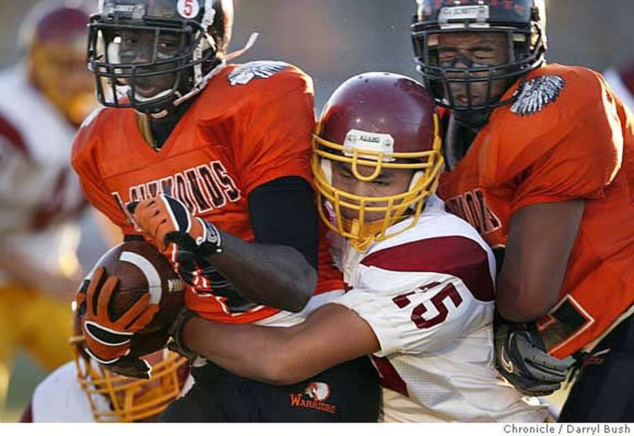 McClymonds' Deante Washington (4) is stopped by Lincoln's Kraig Shrader (25) in the 1st qtr. as high schools; McClymonds of Oakland vs. Lincoln of San Francisco in the first Transbay Championship, at Laney college in Oakland, CA, on Friday, December, 1, 2006. McClymonds won the game. 12/1/06  Darryl Bush / The Chronicle ** roster (cq) Photo: Darryl Bush