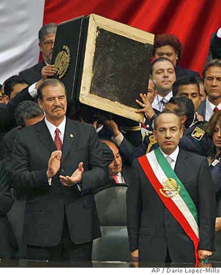 ** ADDS INFORMATION ABOUT THE PODIUM ** Mexican President Felipe Calderon, right, stands wearing the presidential sash as outgoing president Vicente Fox looks on at the National Congress during his inauguration ceremony amidst a congress partially seized by lawmakers who tried unsuccessfully to block his swearing in ceremony in Mexico City on Friday Dec. 1, 2006. Calderon asked members of his security to remove the podium so the presidential sash could be seen in its entirety. (AP Photo/Dario Lopez-Mills) **EFE OUT** Photo: DARIO LOPEZ-MILLS