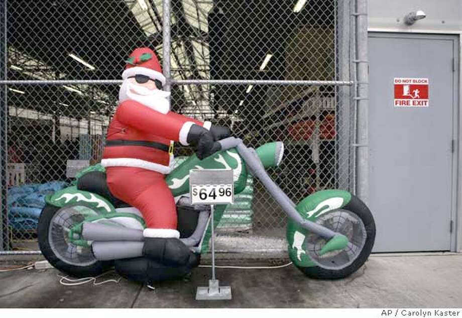 An inflatable Santa Claus riding a chopper is for sale at a Wal-Mart store in Harrisburg, Pa., Thursday, Nov. 30, 2006. Wal-Mart Stores Inc. issued a sobering warning for the holiday shopping season, predicting its December same-store sales gain would be no better than 1 percent. (AP Photo/Carolyn Kaster) Photo: CAROLYN KASTER