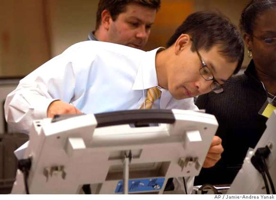 ** FILE ** Michael Vu, director of the Cuyahoga County Board of Elections, works with a voting machine as votes continue to be counted into the early morning at the Cuyahoga County Board of Elections in Cleveland, Wednesday, Nov. 8, 2006. The commissioners of the state's most populous county are considering getting rid of its touch-screen voting machines and putting a new system in place for the presidential election in 2008. (AP Photo/Jamie-Andrea Yanak) FILE PHOTO Photo: JAMIE-ANDREA YANAK