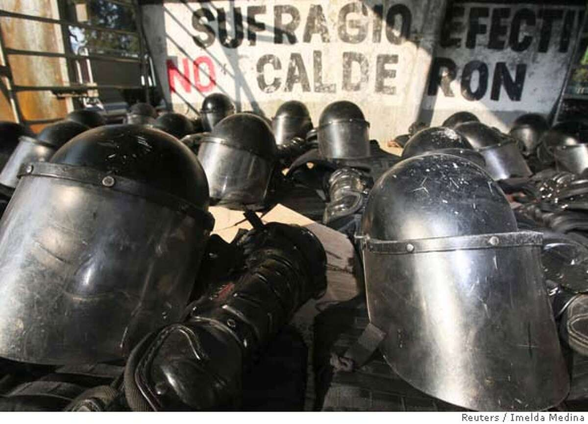 """Riot equipment is seen laid out on the floor near Mexico's congress in Mexico City November 30 as security is stepped up ahead of Felipe Calderon's swearing as the new President on Friday. Calderon defied leftist protesters on Thursday by vowing to hold his inauguration in Congress despite a sit-in there by opposing lawmakers who say he won the July election by fraud. The graffiti in the background reads """"Efective suffrage, no calderon"""" in Spanish. REUTERS/Imelda Medina (MEXICO) 0"""