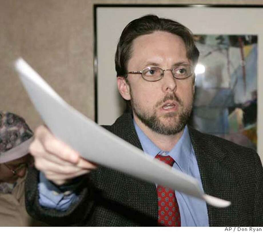 Brandon Mayfield hands out copies of a statement regarding his lawsuit against the FBI in Portland, Ore., Wednesday, Nov. 29, 2006. Mayfield, wrongly arrested by the FBI in the 2004 Madrid train bombings, announced he has settled his lawsuit against the agency for $2 million. (AP Photo/Don Ryan) Photo: DON RYAN