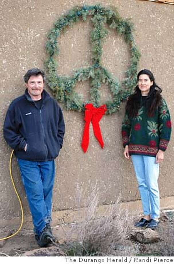 Bill Trimarco and Lisa Jensen stand next to their peace wreath at their home near Pagosa Springs, Colo., Friday, Nov. 24, 2006. The couple received a letter Tuesday from their subdivisions homeowners association telling them to take down the sign or face a fine of $25 (euro 19) per day. (AP Photo/The Durango Herald, Randi Pierce) **MANDATORY CREDIT** MANDATORY CREDIT Photo: RANDI PIERCE