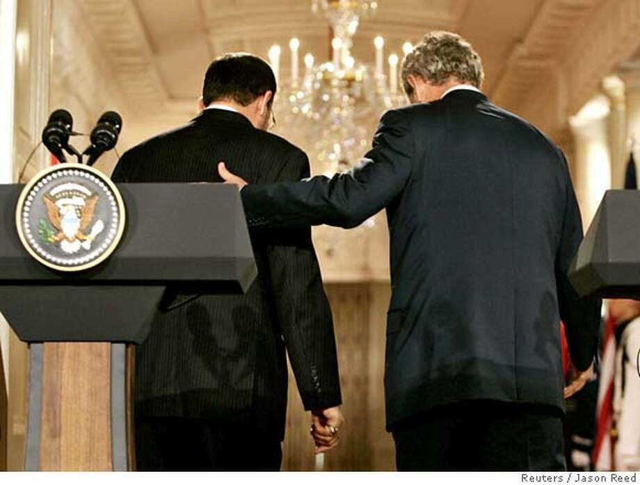 U.S. President George W. Bush (R) escorts Iraqi Prime Minister Nuri al-Maliki from the stage at the end of their news conference at the White House in Washington, July 25, 2006. REUTERS/Jason Reed (UNITED STATES)  Ran on: 07-26-2006  President Bush and Iraqi Prime Minister Nouri al-Maliki (left) leave after their news conference.  Ran on: 07-26-2006  President Bush and Iraqi Prime Minister Nouri al-Maliki (left) leave after their news conference. 0 Photo: JASON REED