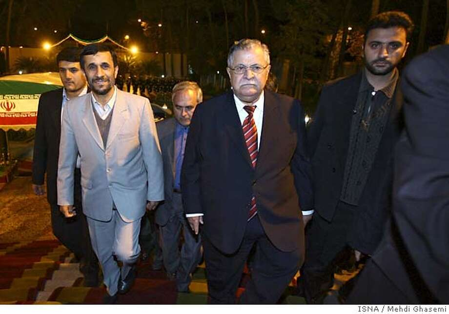 Iranian President Mahmoud Ahmadinejad, left, and Iraqi President Jalal Talabani, center, arrive for their meeting in Tehran, Iran, Monday, Nov. 27, 2006. Iraqi President Jalal Talabani sought Monday to enlist Iran's help in quelling the spiraling violence that threatens to tear his country apart. He arrived in Tehran with a delegation of Iraqi officials and headed to Iran's Presidential Palace to meet with President Mahmoud Ahmadinejad, whose government has been trying to organize a summit joining Iran, Iraq and Syria in a bid to assert the Islamic Republic's role as a regional power broker. (AP Photo/ISNA, Mehdi Ghasemi) Photo: MEHDI GHASEMI