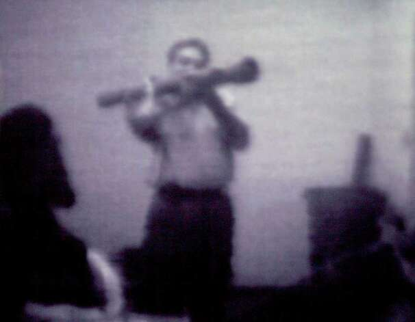 Still image from a surveillance videotape shows informant Shahed Hussain wielding an inert, inoperable shoulder-fired rocket launcher to suspects in a federal terrorism sting in Albany (Times Union archive)