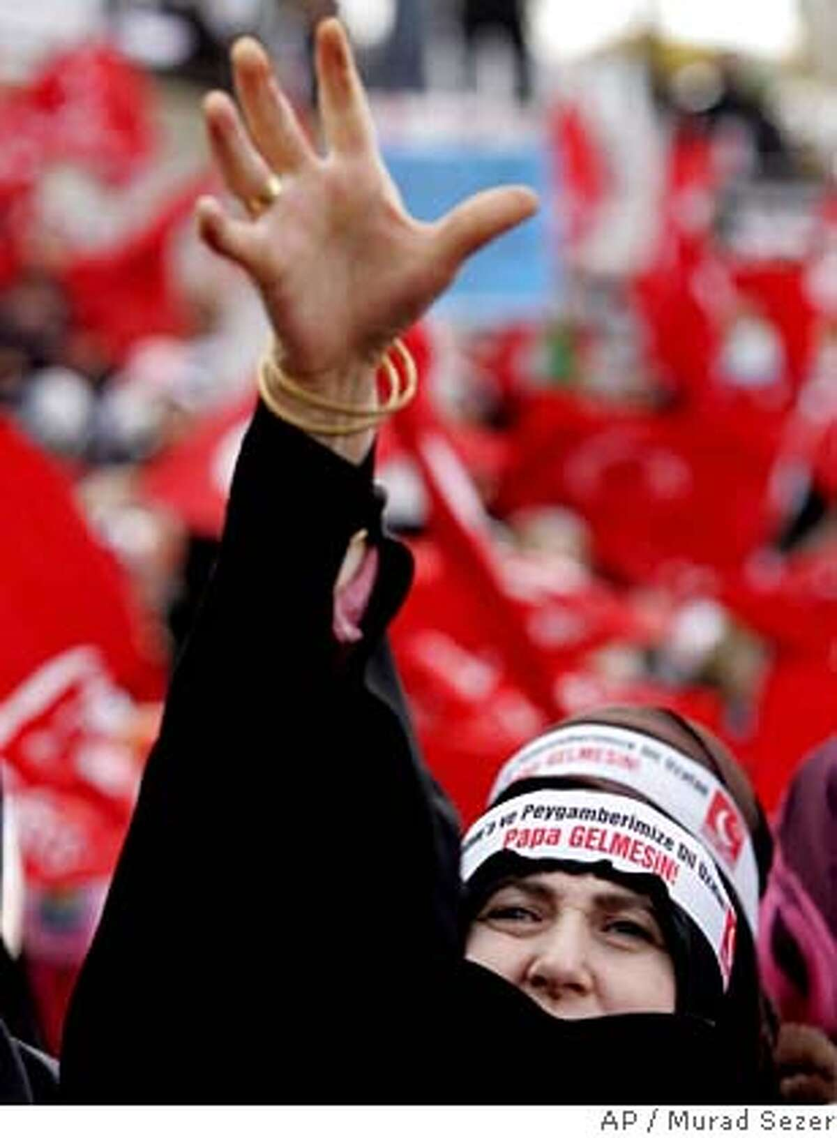 """A Turkish woman, wearing a headband that reads:""""The ignorant and sneaky pope who insulted Islam and our Prophet should not come to Turkey"""", chants Islamic slogans during an anti-pope rally in Istanbul, Turkey, Sunday, Nov. 26, 2006. Thousands of Turks gathered in an Istanbul square to protest against the upcoming visit of Pope Benedict XVI, planned for Tuesday, to this predominantly Muslim country. (AP Photo/Murad Sezer)"""