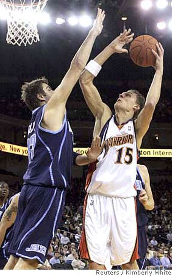 Golden State Warriors Andris Biedrins (R) goes up for a shot against Utah Jazz Mehemet Okur in the first half of an NBA basketball game in Oakland, California, November 25, 2006. REUTERS/Kimberly White (UNITED STATES) Photo: KIMBERLY WHITE