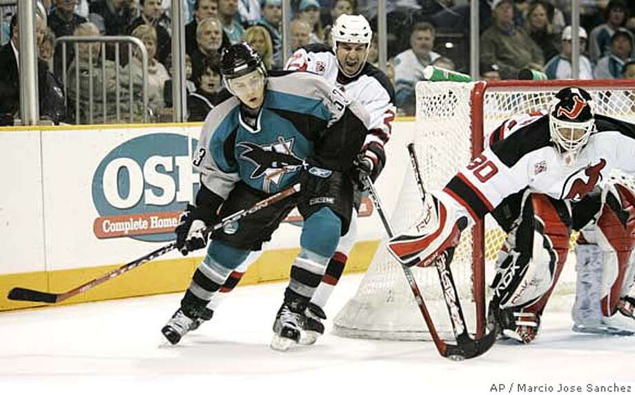 From left, San Jose Sharks center Joe Pavelski is defended by New Jersey Devils defenseman Brad Lukowich and goalie Martin Brodeur in the second period of a NHL hockey game in San Jose, Calif., Saturday, Nov. 25, 2006.(AP Photo/Marcio Jose Sanchez) Photo: MARCIO JOSE SANCHEZ
