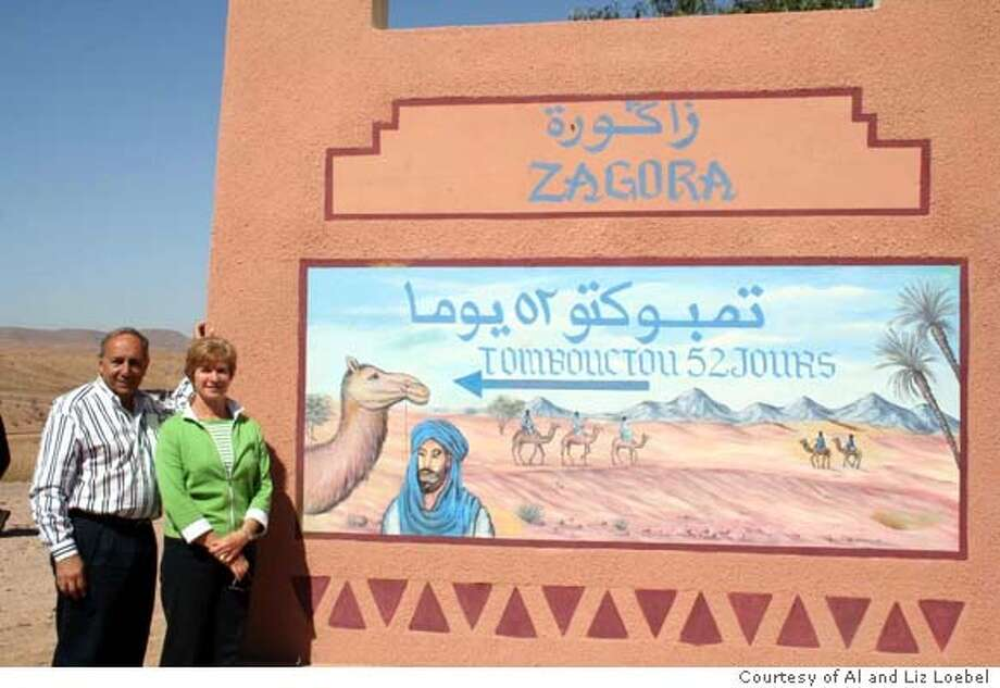Nov. 26  TRAVEL JUSTBACK -- Al and Liz Loebel in town of Zagora. Sign says in French that Timbuktu is a 52 day ride by camel. 2/21/06 in , . / Special to The Chronicle Ran on: 11-26-2006  Al and Liz Loebel pose by a sign in the Moroccan town of Zagora that says Timbuktu is 52 days away by camel. Photo: All And Liz Loebel
