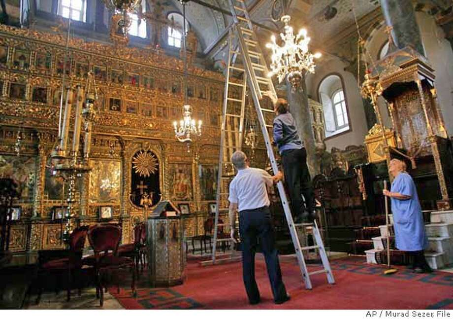 Workers set up lightining and audio systems for the upcoming pope visit at the patriarchal cathedral of St. George in the Orthodox Patriarchate, house of the Ecumenical Patriarch Bartholomew I, in Istanbul, Turkey, Saturday, Nov. 25, 2006. Pope Benedict XVI will arrive in Turkey, his first visit to a Muslim country as pontiff, on Tuesday Nov. 28. The pope's visit to Turkey was born out of Benedict's desire to meet Bartholomew, who has his headquarters in Istanbul, once ancient Constantinople. The pontiff has been trying to foster better relations between the Orthodox and Catholics, and will meet privately with Bartholomew at the patriarchate on Nov. 29. (AP Photo/Murad Sezer) Photo: MURAD SEZER