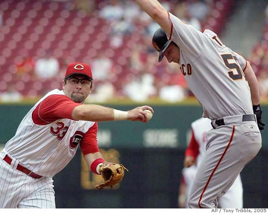 Cincinnati Reds' Rich Aurilia, left, tags San Francisco Giants' Brett Tomko out before throwing to first base, getting batter Randy Winn and completeing a double play in the third inning in Cincinnati, Thursday, Aug. 18, 2005. (AP Photo/Tony Tribble) Ran on: 08-19-2005  Ken Griffey Jr. connects for a two-run home run in the first inning off Brett Tomko. Ran on: 08-19-2005  Ken Griffey Jr. connects for a two-run home run in the first inning off Brett Tomko. Ran on: 01-09-2006 Ran on: 01-09-2006 Photo: TONY TRIBBLE