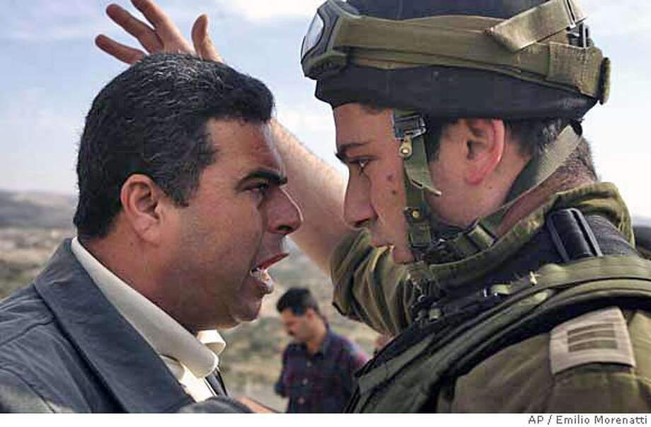 A Palestinian demonstrator and an Israeli army officer argue during a protest against the building of Israel's separation barrier in the West Bank village of Bilin, near Ramallah, Friday, Nov. 24, 2006. (AP Photo/Emilio Morenatti) Photo: EMILIO MORENATTI